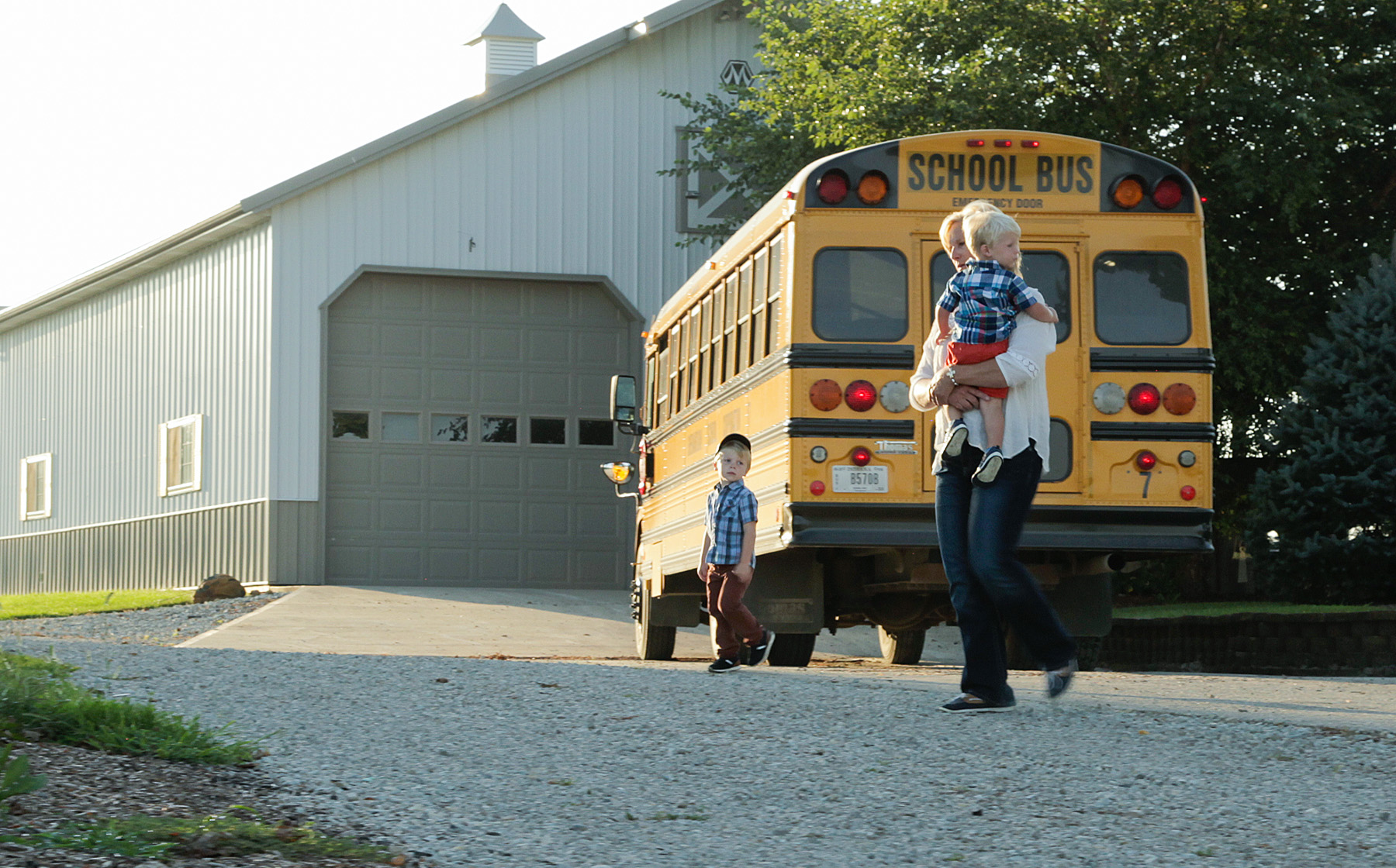 Image of Keesling Farms Growers for Red Gold Tomatoes Kim Keesling wife holding grandchild at the back of a school bus