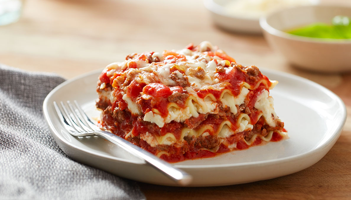 Image of Classic Lasagna on white plate with a fork