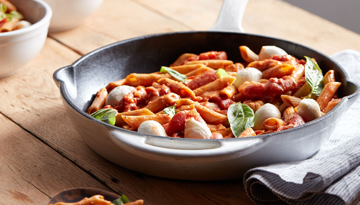 Image of Creamy Caprese Pasta with penne pasta mozzarella balls basil and torn whole peeled tomatoes in skillet