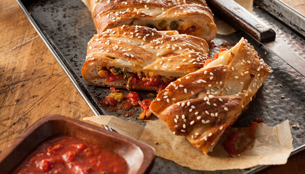 Image of Pizza stromboli cut into slices on sheet tray