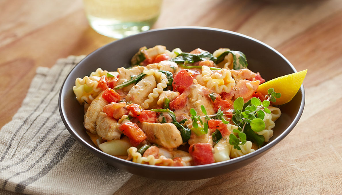 Image of Red Gold recipe Creamy Chicken Florentine Pasta in black bowl and diced tomatoes