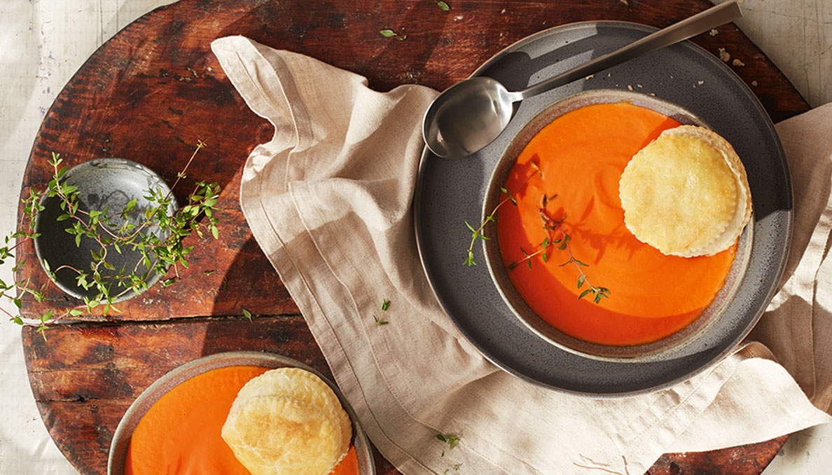 Image of two bowls of Tomato soup with puff pastry  in bowl on wood cutting board
