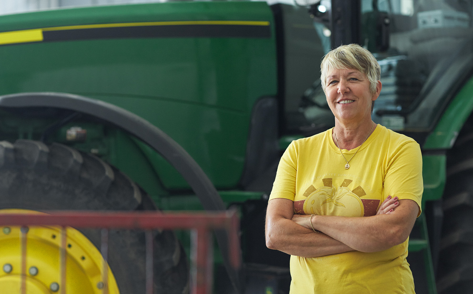Image of Janice AcMoody wife to Vern who is a Red Gold Tomato grower standing in front of green tractor