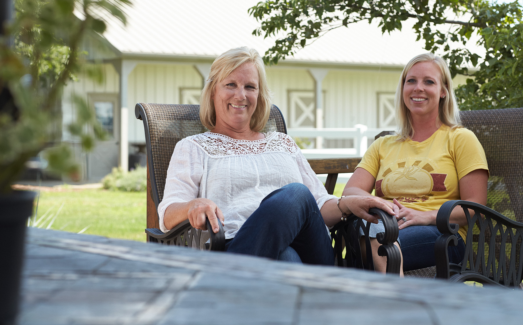 Image of Keesling Farms Growers for Red Gold Tomatoes Kim and daughter Kaycie in chairs outside with barn in background