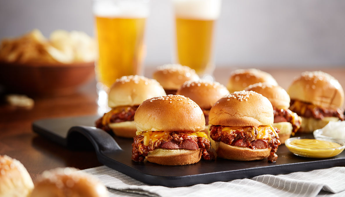 Image of Chili Cheesedog Sliders on tray with glasses of beer in background