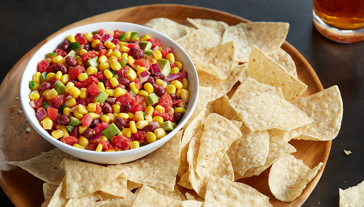 Image of Corn Salsa on wood tray with tortilla chips