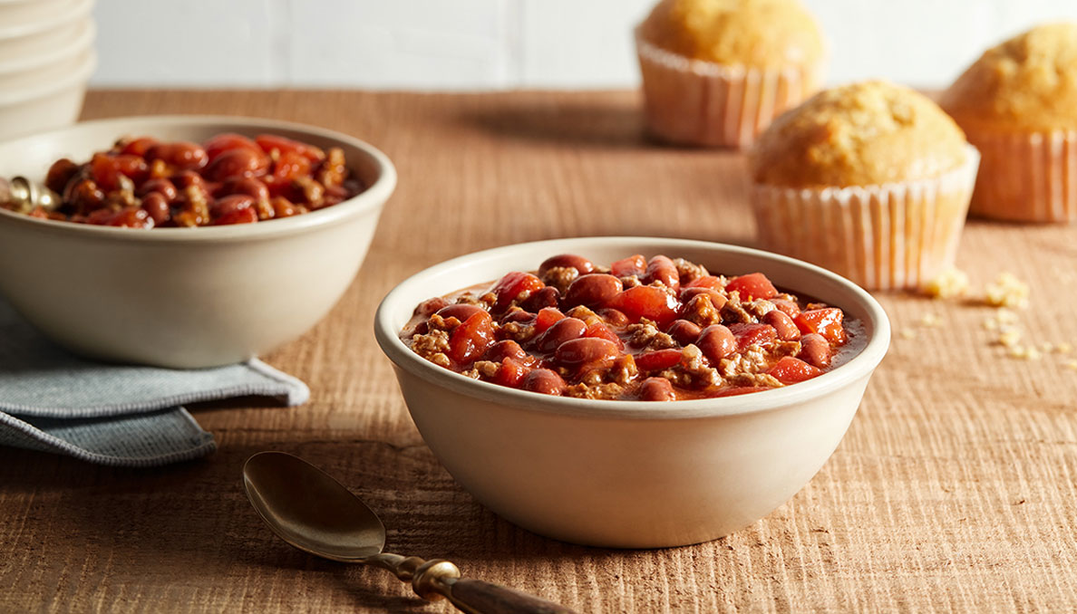 Image of two bowls of Red Gold perfect chili with cornbread muffins in background