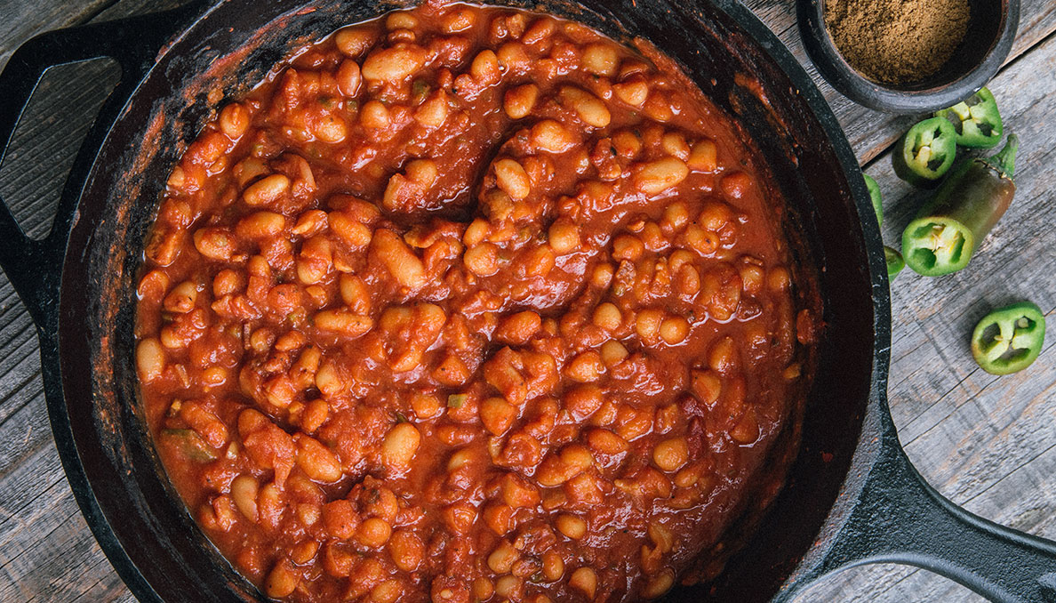 Image of Redneck Riviera BBQ Baked Beans in cast iron skillet