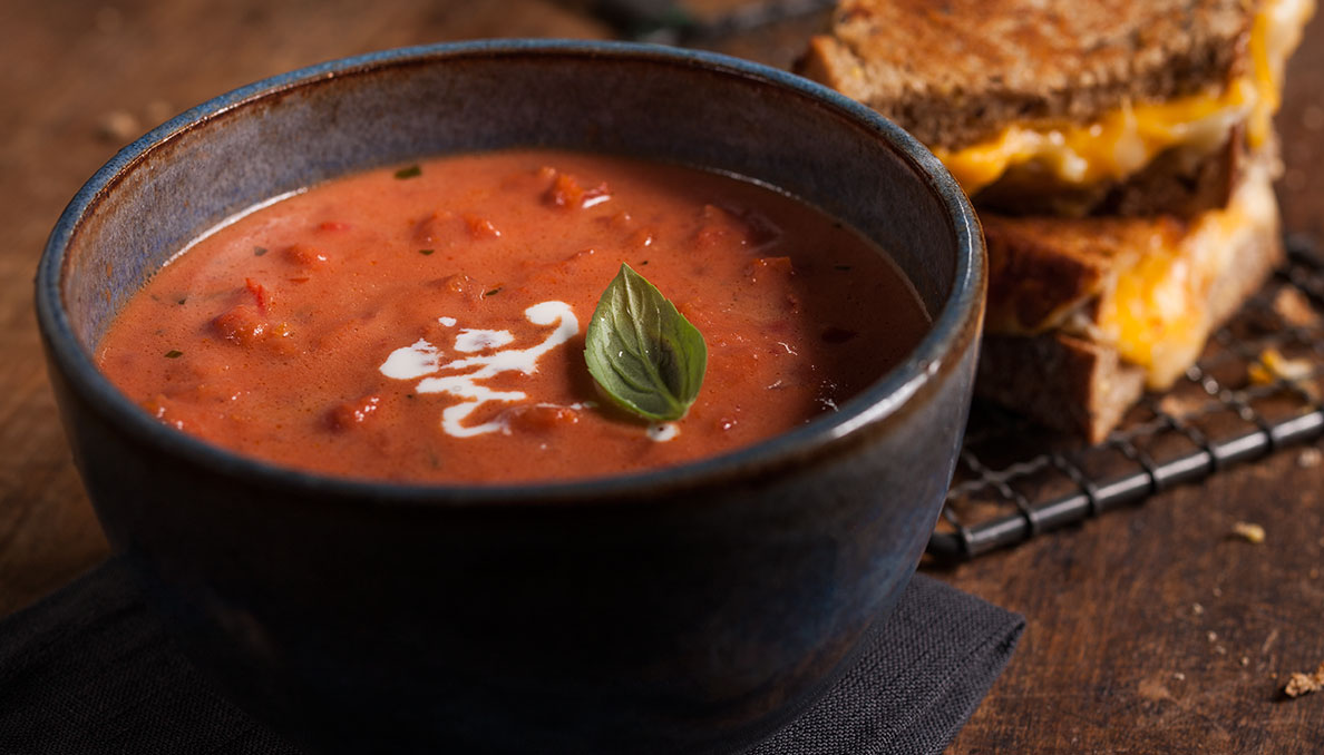 Image of Tomato basil soup with grilled cheese in the background