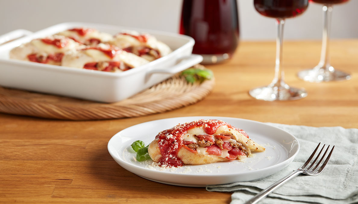 Image of pizza stuffed chicken on white plate and casserole dish in background on wood table
