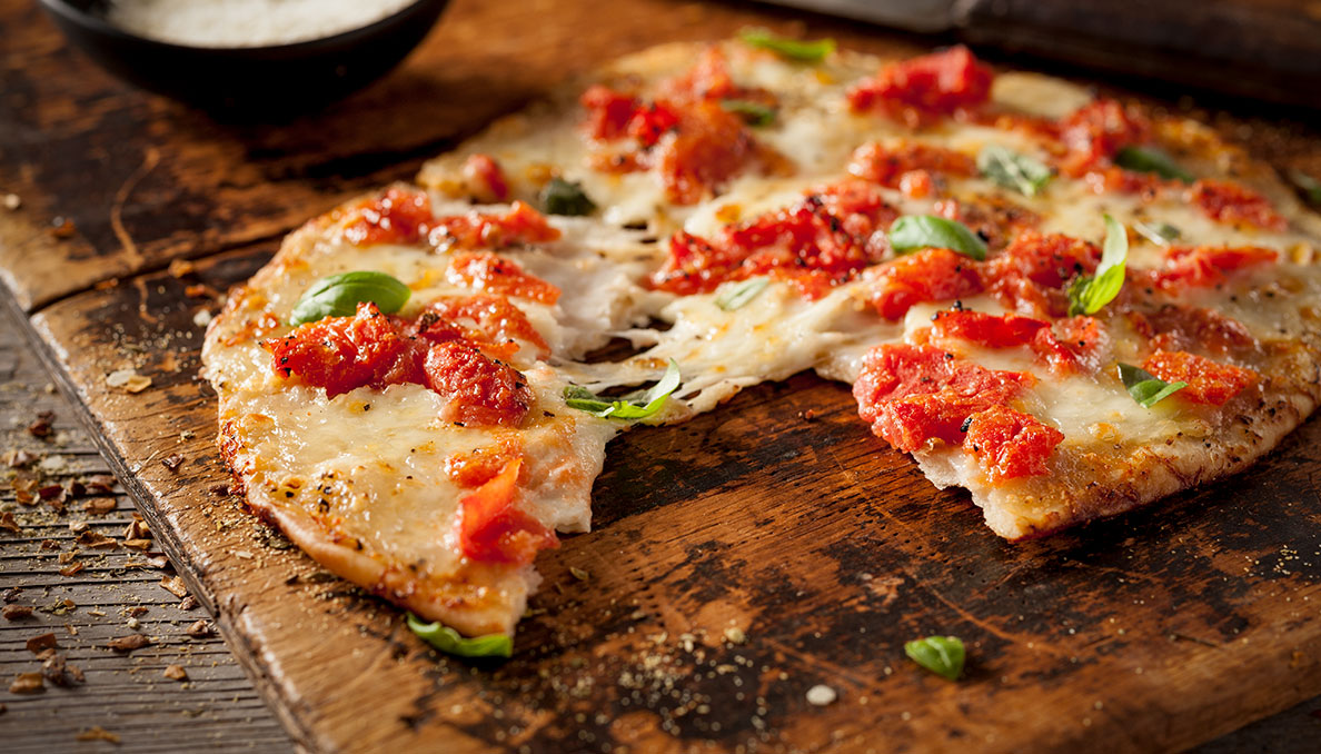 Image of thin crust pizza topped Red Gold tomatoes and melted cheese