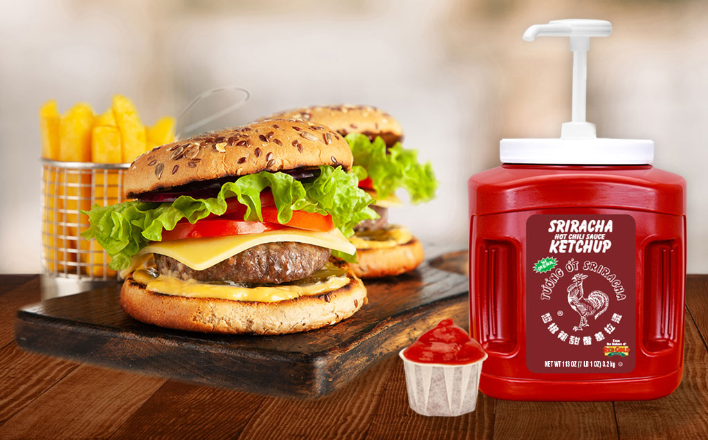 Image of two burgers next to a ketchup pump dispenser of red gold sriracha ketchup