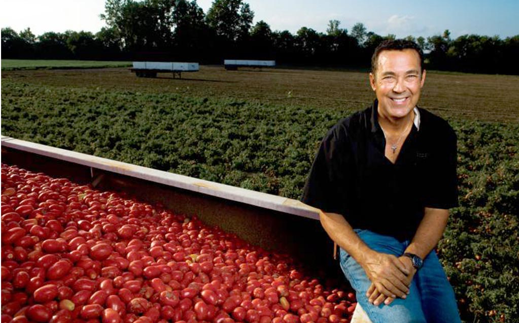 Image of grower sitting on side of tomato trailer full of red tomatoes from tomato field